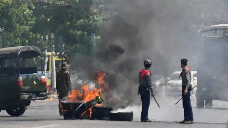 La policía está parada junto a una barricada de neumáticos improvisada en llamas, erigida por manifestantes que se manifestaban contra el golpe militar, en el municipio de Rangún, Birmania, en el sur de Okkalapa el 1 de abril de 2021. (STR / AFP vía Getty Images)