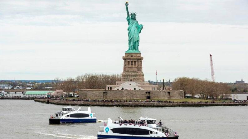 Fotografía cedida el 21 de abril de 2021 por NYC & Company, oficina de promoción turística de Nueva York, donde se ven dos ferris navegando con turistas frente a la Estatua de la Libertad, en Liberty Island (EE.UU). EFE/NYC & Company /C. Taylor Crothers