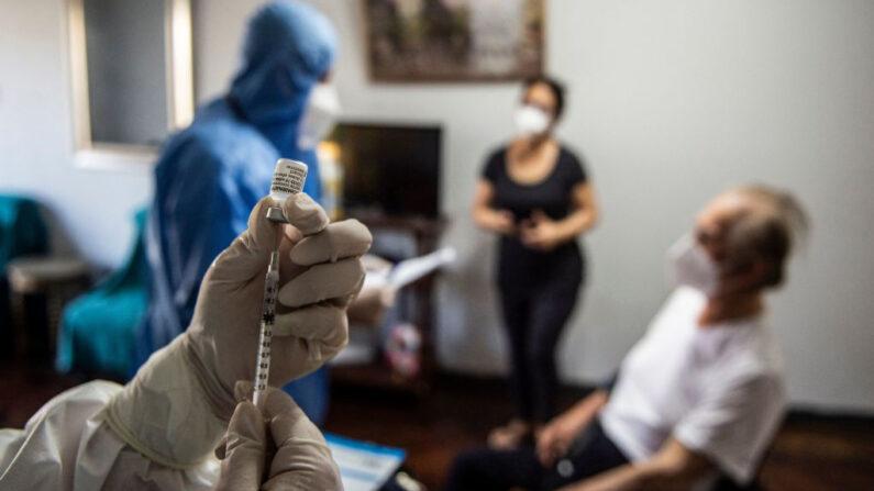 Un trabajador de salud prepara una dosis de la vacuna Pfizer-BioNTech COVID-19 para Antonio Ferrari (92), en su casa de Lima el 8 de marzo de 2021, mientras Perú inicia la vacunación de ancianos, policías y militares. (Ernesto Benavides / AFP vía Getty Images)
