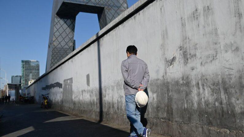 Un trabajador, visto sosteniendo su casco, camina hacia un sitio de construcción en Beijing el 23 de enero de 2019. (WANG ZHAO/AFP vía Getty Images)