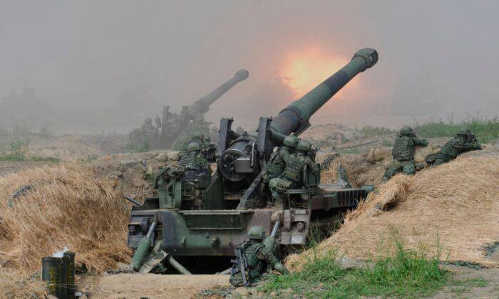 """Varios soldados disparan dos cañones de artillería autopropulsados de 8 pulgadas durante el 35º ejercicio militar """"Han Kuang"""" en el Condado de Pingtung, al sur de Taiwán, el 30 de mayo de 2019. (Sam Yeh/AFP vía Getty Images)"""