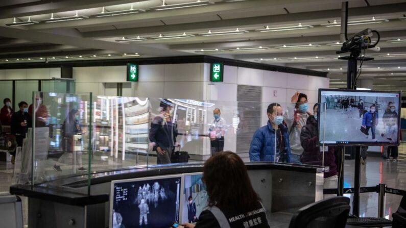 Personal de salud del aeropuerto monitorea a los pasajeros en una sala de llegadas dentro del Aeropuerto Internacional de Hong Kong el 21 de febrero de 2020. (VIVEK PRAKASH/AFP a través de Getty Images)