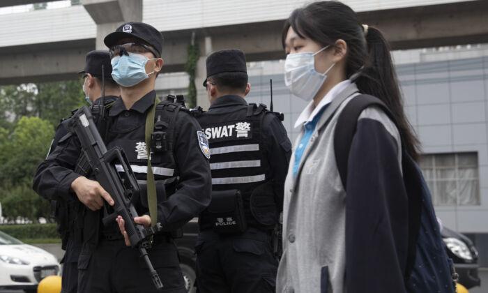 Agentes de policía (i) hacen guardia en la entrada de una escuela secundaria mientras una estudiante de último año pasa cerca de ellos en Wuhan, China, el 6 de mayo de 2020. (STR/AFP vía Getty Images)
