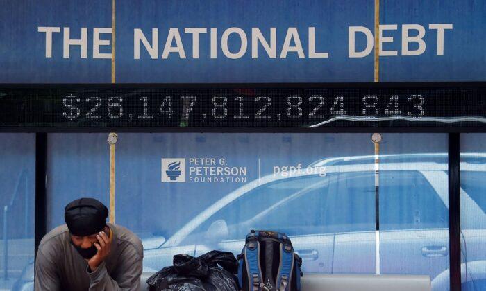 Un hombre espera en una parada de autobús que muestra la deuda nacional de Estados Unidos, en Washington, D.C., el 19 de junio de 2020. (Olivier Douliery/AFP a través de Getty Images)
