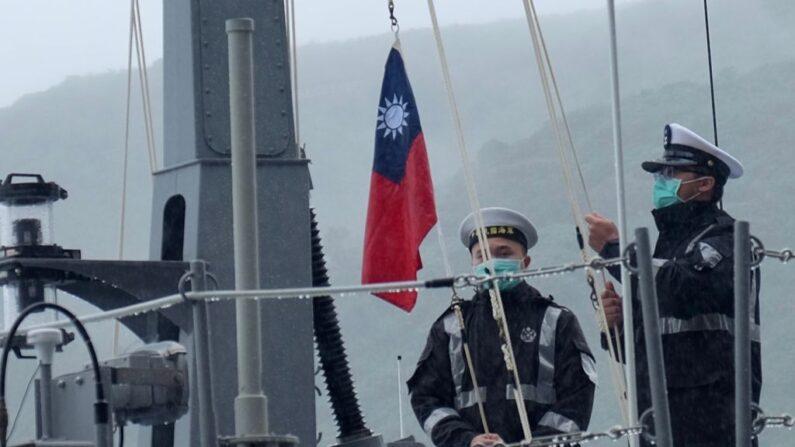 Dos soldados de la armada taiwanesa izan la bandera nacional en la primera lancha rápida nacional de colocación de minas durante una ceremonia oficial en un astillero en Suao, en el condado de Yilan, al este de Taiwán, el 15 de diciembre de 2020. (Sam Yeh / AFP vía Getty Images)