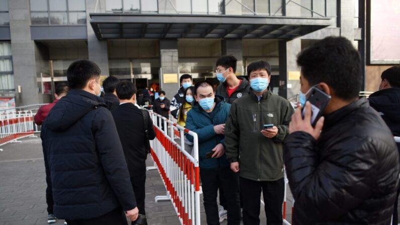 Residentes hacen fila frente a un centro comunitario para vacunarse contra el COVID-19 en Beijing el 12 de enero de 2021. (GREG BAKER/AFP a través de Getty Images)