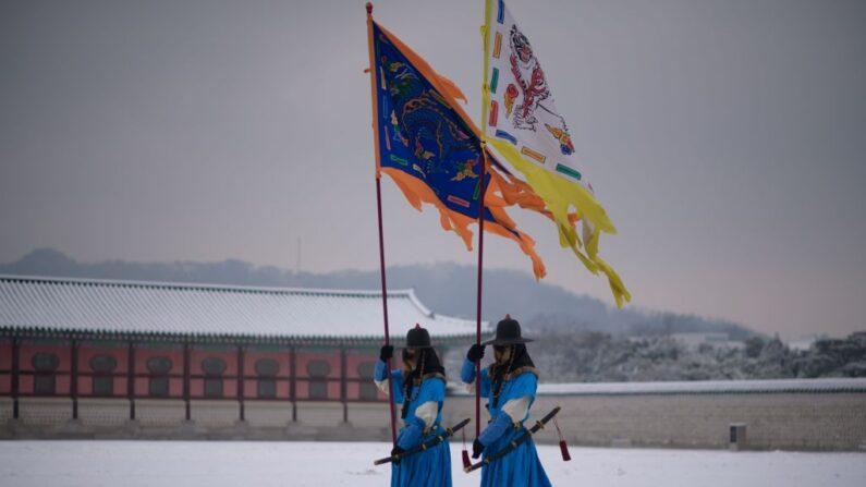 Actores representan a guardias reales caminando por la nieve en el palacio Gyeongbokgung en el centro de Seúl el 28 de enero de 2021 (Ed Jones/AFP vía Getty Images)