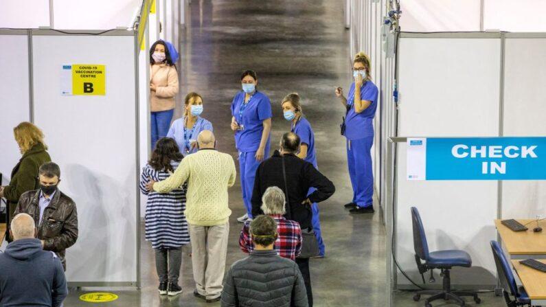 Miembros del público esperan para recibir una dosis de la vacuna AstraZeneca/Oxford Covid-19 en el SSE Arena que se ha convertido en un centro de vacunación temporal, en Belfast, Irlanda del Norte, el 29 de marzo de 2021. (Paul Faith/AFP vía Getty Images)