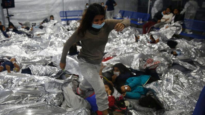 Una menor camina sobre otras dentro de una cápsula para menores de edad de sexo femenino, en el centro de alojamiento del Departamento de Seguridad Nacional, administrado por la Oficina de Aduanas y Protección Fronteriza (CBP), en Donna, Texas, el 30 de marzo de 2021. (Dario Lopez-Mills - Pool/Getty Images)