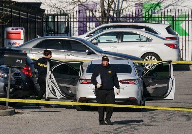 Los investigadores de la escena del crimen caminan por el estacionamiento del lugar del tiroteo masivo en una instalación de FedEx en Indianápolis, Indiana, el 16 de abril de 2021. (JEFF DEAN/AFP vía Getty Images)