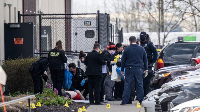 (NOTA DEL EDITOR: La imagen representa una muerte) Un grupo de investigadores de la escena del crimen se reúnen alrededor de un cuerpo en el estacionamiento de  FedEx el 16 de abril de 2021 en Indianápolis, Indiana. La zona es el escenario de un tiroteo masivo que dejó al menos ocho muertos y cinco heridos en la noche del 15 de abril. ( Jon Cherry/Getty Images)