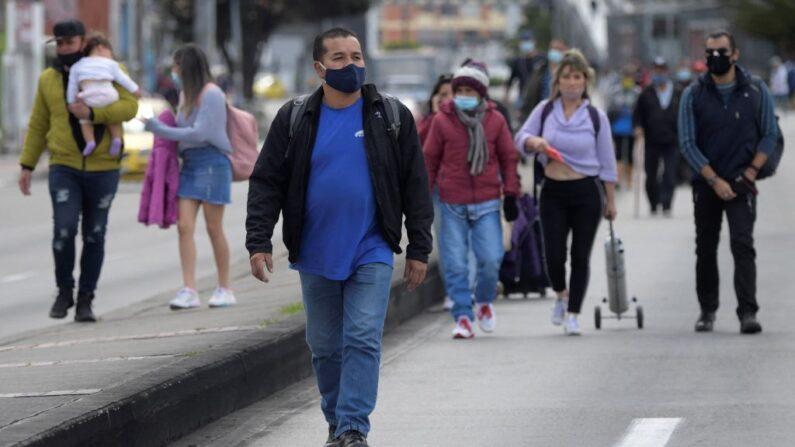 La gente camina a lo largo de una carretera mientras los comerciantes la bloquean durante una protesta contra la cuarentena obligatoria impuesta por el Gobierno colombiano para el próximo fin de semana en algunas de las principales ciudades del país para prevenir los contagios de covid-19, en Bogotá, el 15 de abril de 2021. (Raul Arboleda/AFP/Getty Images)