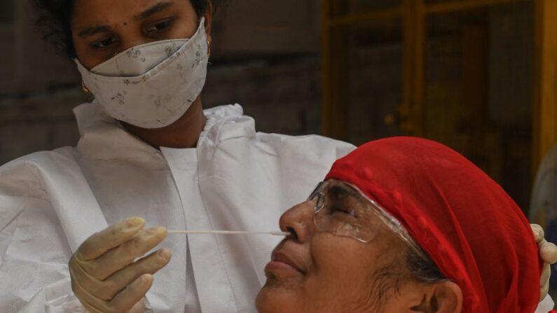 Una personal médico toma un hisopo nasal para una prueba rápida de antígeno (RAT) en medio del aumento de los casos de covid-19, en Mumbai, India, el 19 de abril de 2021. (Indranil Mukherjee/AFP vía Getty Images)