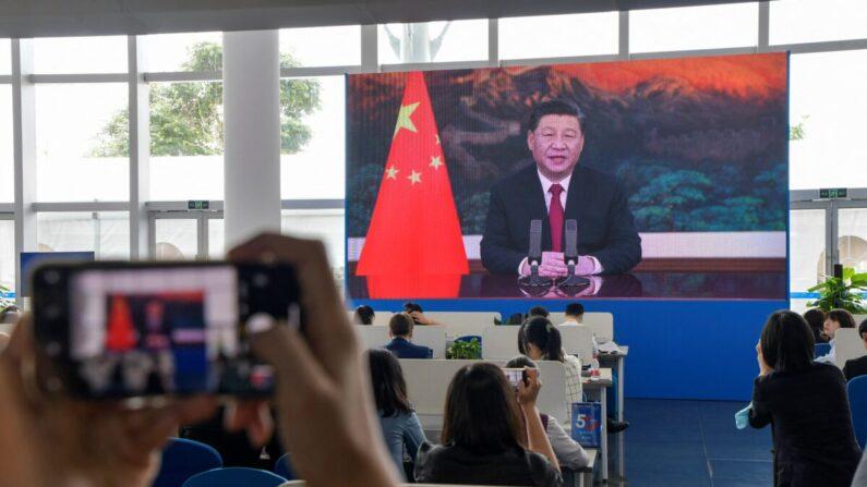 Un grupo de periodistas observa una pantalla que muestra al mandatario chino Xi Jinping pronunciando un discurso durante la inauguración de la Conferencia Anual 2021 del Foro de Boao para Asia (BFA) en Boao, China, el 20 de abril de 2021. (STR/AFP vía Getty Images)