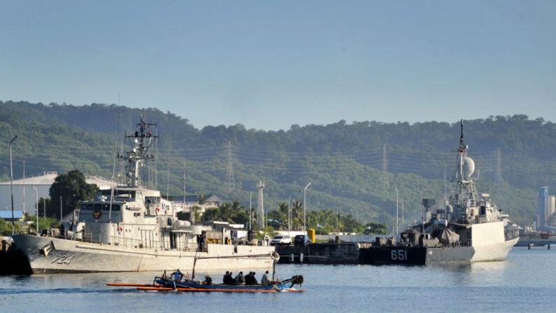 Una canoa outrigger navega frente a los barcos de la Armada de Indonesia en la base naval de Banyuwangi, provincia de Java Oriental, el 24 de abril de 2021, mientras los militares continúan las operaciones de búsqueda del submarino KRI Nanggala de la Armada que desapareció el 21 de abril durante un ejercicio de entrenamiento. (Sonny Tumbelaka/AFP vía Getty Images)