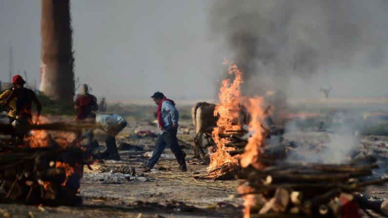 Familiares y allegados son vistos alrededor de las piras ardientes de las víctimas que perdieron la vida a causa del covid-19 en Daraganj Ghat, cerca de Sangam, la confluencia de los ríos Ganges, Yamuna y el mítico Saraswati, en Allahabad (India), el 26 de abril de 2021. (Sanjay Kanojia / AFP vía Getty Images)