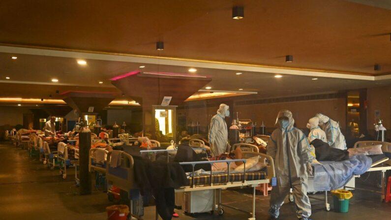 Trabajadores sanitarios con equipos de protección personal atienden a pacientes positivos al covid-19 en el interior de una sala de banquetes convertida temporalmente en un centro de atención al covid, en Nueva Delhi, India, el 29 de abril de 2021. (Tauseef Mustafa/AFP vía Getty Images)