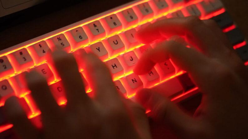 En esta ilustración fotográfica, un joven tipea en un teclado de computadora iluminado. (Sean Gallup/Getty Images)