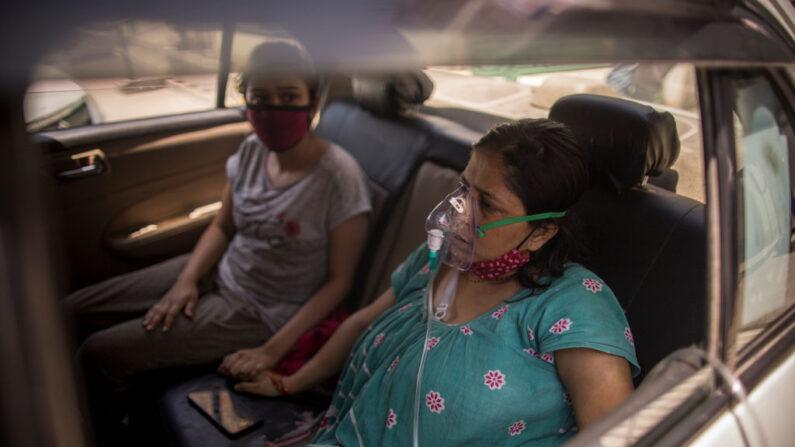 Una paciente infectada por el covid-19 lleva máscaras de oxígeno mientras se suministra oxígeno gratuito como parte del servicio público para las personas necesitadas en un Gurdwara o lugar sagrado sij en medio de la creciente preocupación por la falta de oxígeno el 24 de abril de 2021 en Nueva Delhi, India. (Anindito Mukherjee/Getty Images)