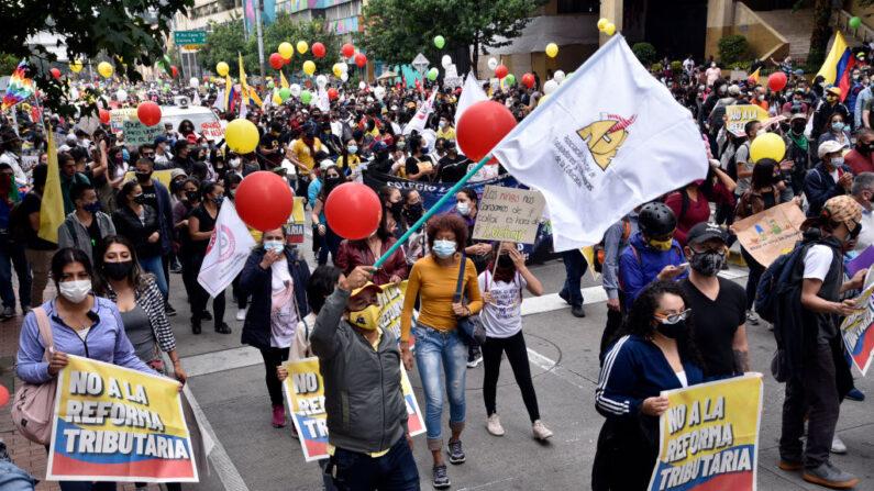 Manifestantes con mascarillas marchan durante el paro nacional contra la reforma tributaria propuesta por el gobierno de Duque el 28 de abril de 2021 en Bogotá, Colombia. (Guillermo Legaria/Getty Images)