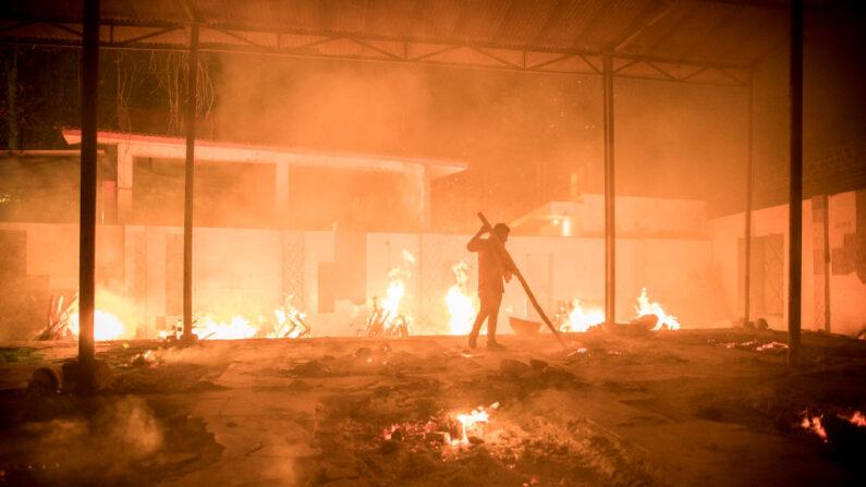 Se ven trabajadores en un crematorio donde arden múltiples piras funerarias para los pacientes que perdieron la vida a causa del covid-19 el 29 de abril de 2021 en Nueva Delhi, India. (Anindito Mukherjee/Getty Images)