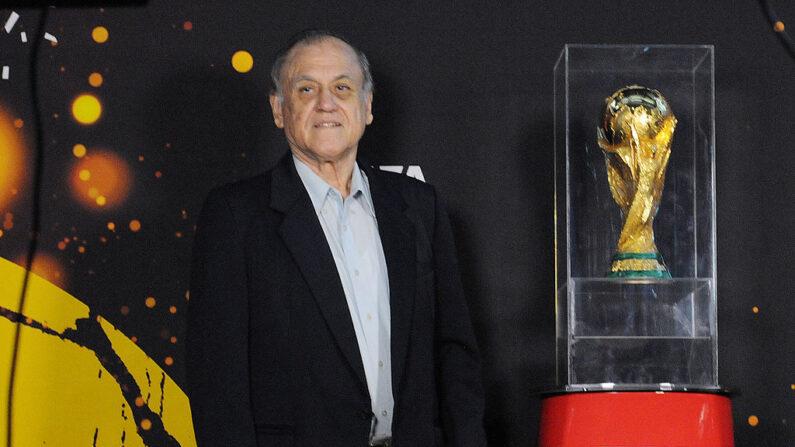 """El entrenador de la selección hondureña de fútbol para España 1982, José de la Paz Herrera alias """"Chelato Uclés"""", posa junto a la Copa Mundial de la FIFA en Tegucigalpa, Honduras, el 1 de octubre de 2013. (Orlando Sierra/AFP vía Getty Images)"""