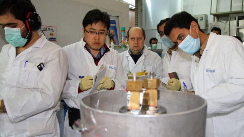 Inspectores del Organismo Internacional de la Energía Atómica (OIEA) no identificados (2º-3º de la izquierda) y técnicos iraníes desconectan las conexiones entre las cascadas gemelas para la producción de uranio al 20 por ciento en el centro de investigación nuclear de Natanz, a unos 300 kilómetros al sur de Teherán, el 20 de enero de 2014. (Kazem Ghane/IRNA/AFP via Getty Images)