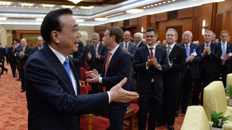 Mark Zuckerberg, CEO de Facebook (segundo a la derecha) y los representantes en el extranjero del Foro de Desarrollo de China aplauden la llegada de Li Keqiang, primer ministro chino (izquierda) durante una reunión en el Gran Salón del Pueblo en Beijing el 21 de marzo de 2016. (Kenzaburo Fukuhara-Pool/Getty Images)