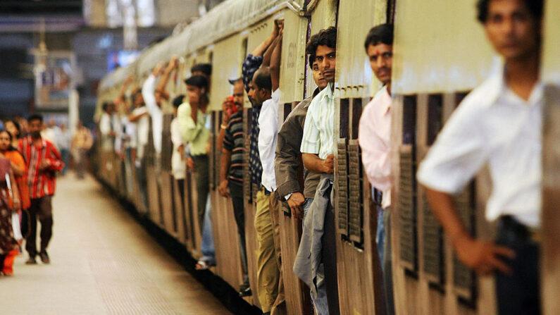 Viajeros permanecen en las puertas de un tren local, mientras sale de la estación de tren de Churchgate, en Mumbai. (INDRANIL MUKHERJEE/AFP via Getty Images)
