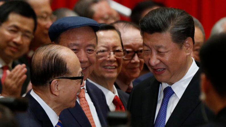 El presidente de China, Xi Jinping (D), es saludado por el magnate hongkonés Li Ka-shing (I) antes de una sesión fotográfica durante la visita de Xi a Hong Kong el 30 de junio de 2017. (BOBBY YIP/AFP vía Getty Images)