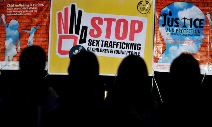 Se corta la silueta de los niños frente a los carteles de la campaña Justicia y protección contra la trata sexual de niños y jóvenes en 2010. (Jay Directo/AFP/Getty Images)