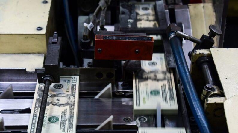 Paquetes de billetes de 20 dólares recién impresos son procesados para su agrupación en la Oficina de Grabado e Impresión del Tesoro de Estados Unidos en Washington, el 20 de julio de 2018. (Eva Hambach/AFP vía Getty Images)
