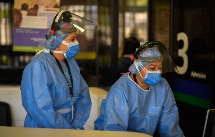 Personal médico trabaja en la entrada de la sala de emergencias para pacientes infectados con Covid-19 en el Centro Médico Docente de Trinidad, en Caracas, el 19 de marzo de 2021. (FEDERICO PARRA/AFP vía Getty Images)