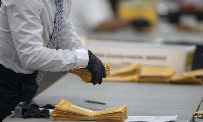Un trabajador del Departamento de Elecciones de Detroit ayuda a clasificar los votos en ausencia en la Junta Central de Recuento en el Centro TCF en Detroit, Michigan, el 4 de noviembre de 2020. (Elaine Cromie/Getty Images)