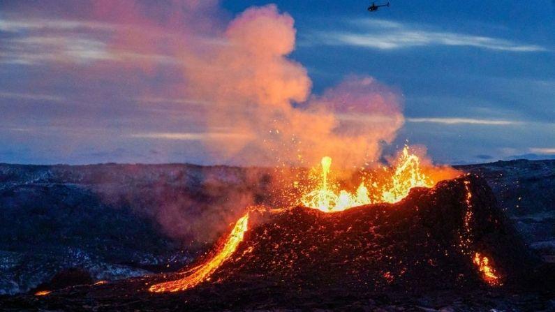 Un helicóptero vuela cerca por encima de la lava que fluye de una fisura cerca del Fagradalsfjall en la península de Reykjanes en Islandia el 6 de abril de 2021. (HALLDOR KOLBEINS/AFP vía Getty Images)