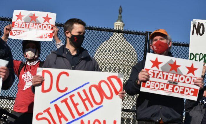 Los activistas sostienen carteles mientras participan en una manifestación en apoyo de la estadidad de D.C., cerca del Capitolio de EE.UU., en Washington D.C., el 22 de marzo de 2021. (Mandel Ngan/AFP a través de Getty Images)