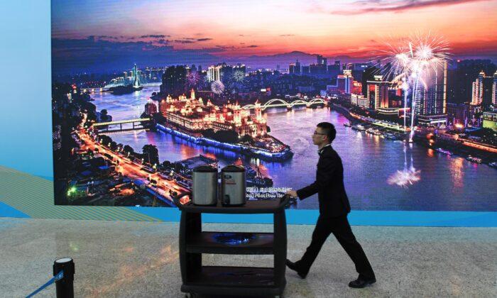 Un trabajador empuja un carrito frente a una pantalla que muestra una foto de la Zona Piloto de Libre Comercio de Fujian, en la sede del Foro de la Franja y la Ruta en Beijing el 26 de abril de 2019. (Greg Baker/AFP vía Getty Images)