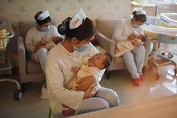 """Las enfermeras sostienen a los bebés en el Centro Xiyuege, o """"Hogar del Mes de la Suerte"""", en Beijing, el 13 de diciembre de 2016. (Greg Baker/AFP vía Getty Images)"""
