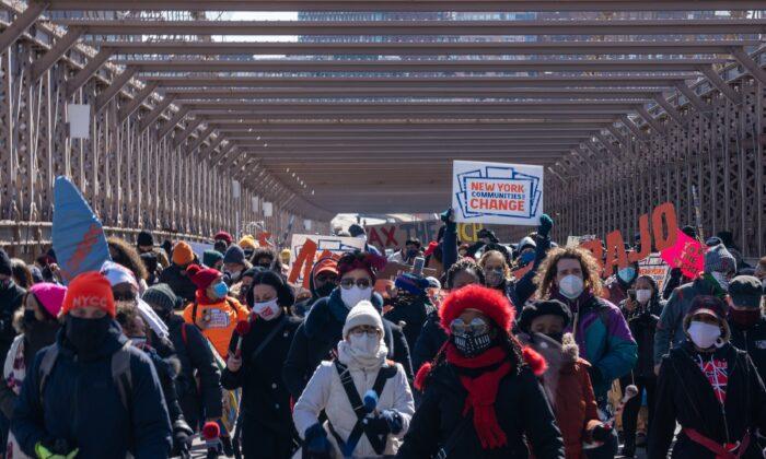 Los manifestantes marchan por el puente de Brooklyn para exigir fondos para los trabajadores excluidos en el presupuesto del estado de Nueva York, en la ciudad de Nueva York, el 5 de marzo de 2021. (David Dee Delgado/Getty Images)