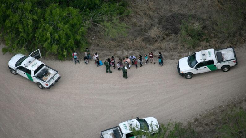 Agentes de la Patrulla Fronteriza de EE.UU. ponen bajo custodia a inmigrantes ilegales, vistos desde un helicóptero del Departamento de Seguridad Pública de Texas, cerca de la frontera entre Estados Unidos y México, en McAllen, Texas, el 23 de marzo de 2021. (John Moore/Getty Images)
