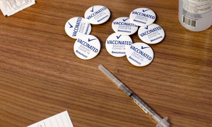 Los pines para los trabajadores de Beaumont Health Care tras recibir su primera dosis de la vacuna Pfizer/BioNTech COVID-19 se observan junto a una jeringa en su centro de servicio en Southfield, Michigan, el 15 de diciembre de 2020. (Jeff Kowalsky/AFP a través de Getty Images)