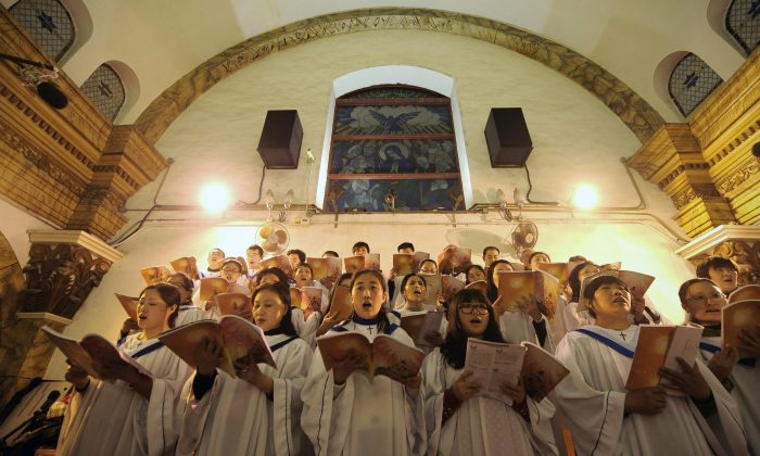 Fieles chinos cantan himnos durante la misa de Nochebuena en una iglesia católica aprobada por el Estado en Beijing el 25 de diciembre de 2012. (Wang Zhao/AFP/Getty Images)