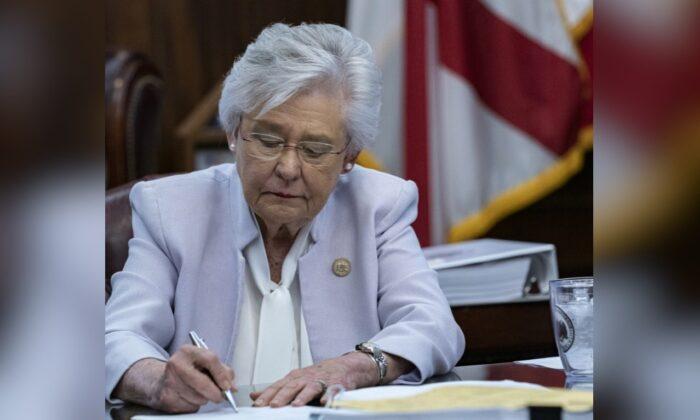 La gobernadora de Alabama, Kay Ivey, firma un proyecto de ley para prohibir los pasaportes con vacunas el 24 de mayo de 2021. (Cortesía de la oficina de la gobernadora Kay Ivey)
