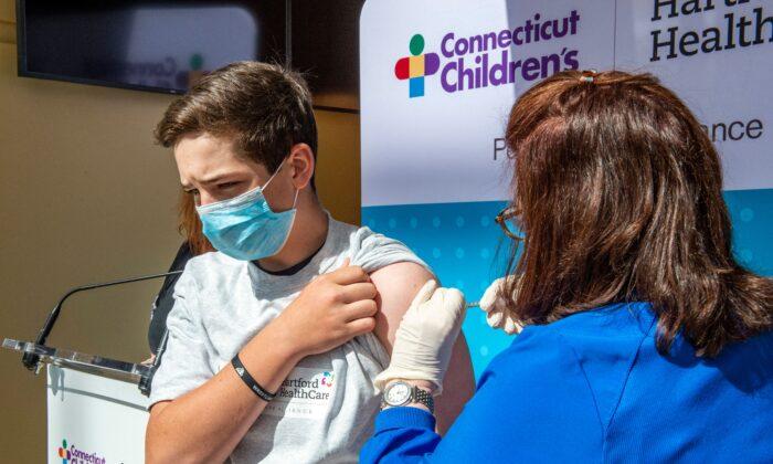 Max Zito, de 13 años, es inoculado por la enfermera Karen Pagliaro en el centro de vacunación masiva de Hartford Healthcares, en el Centro de Convenciones de Connecticut en Hartford (Connecticut), el 13 de mayo de 2021. (Joseph Prezioso/AFP a través de Getty Images)
