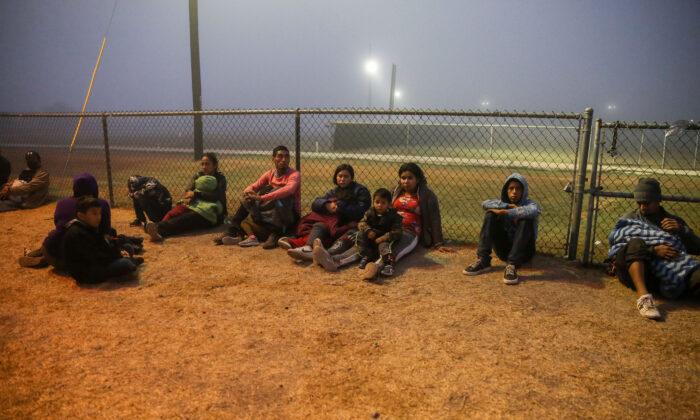 Un grupo de inmigrantes ilegales espera a la Patrulla Fronteriza tras cruzar la frontera entre Estados Unidos y México en La Joya, Texas, el 10 de abril de 2021. (Charlotte Cuthbertson/The Epoch Times)