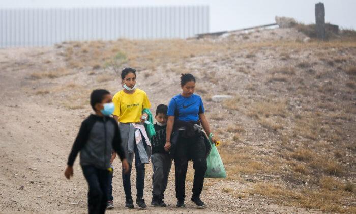Un grupo de inmigrantes ilegales camina hacia los agentes de la Patrulla Fronteriza después de cruzar la frontera entre Estados Unidos y México, en La Joya, Texas, el 10 de abril de 2021. (Charlotte Cuthbertson/The Epoch Times)