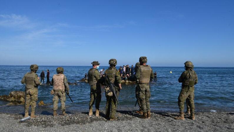 Soldados españoles montan guardia mientras los inmigrantes permanecen en las rocas frente a la costa del enclave español de Ceuta, el 18 de mayo de 2021. (Antonio Sempere / AFP vía Getty Images)