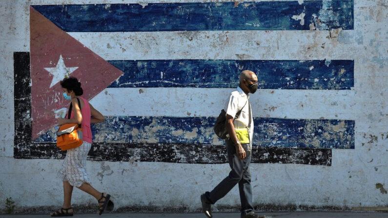 Personas caminan cerca de un mural que representa una bandera cubana en La Habana, Cuba, el 16 de abril de 2021. (Yamil Lage/AFP vía Getty Images)