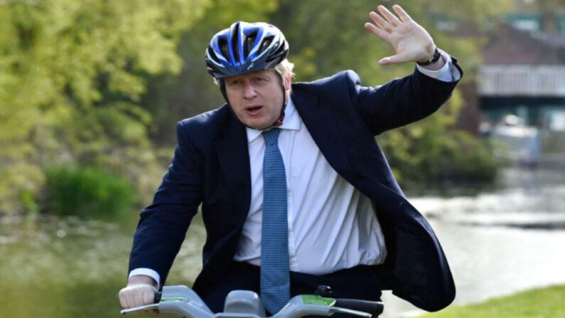 El primer ministro británico, Boris Johnson, monta en bicicleta cerca del camino de sirga del canal de Stourbridge durante una visita a las elecciones locales del partido conservador en Stourbridge, en el centro de Inglaterra, el 5 de mayo de 2021. (Rui Vieira / POOL / AFP vía Getty Images)