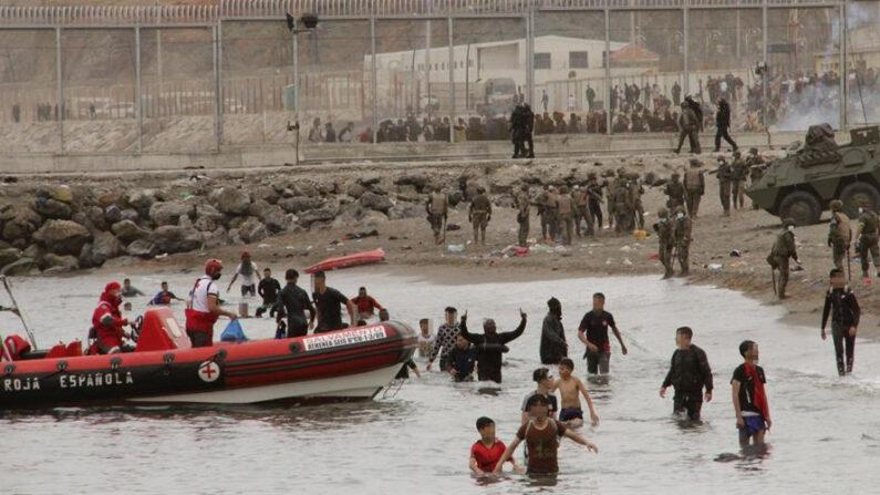 Miembros de la Cruz Roja ayudan a un grupo de inmigrantes menores que han logrado cruzar uno de los espigones fronterizos de Ceuta. EFE/Reduan
